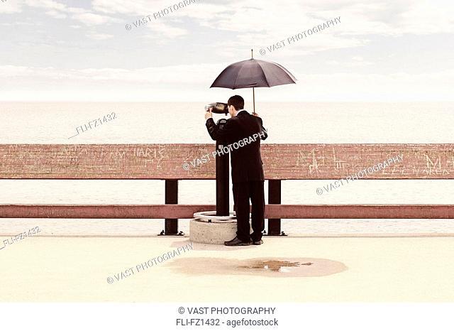 Man in suit holding umbrella, looking through binoculars