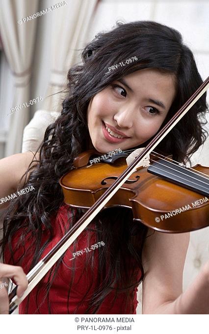 a fashionable woman playing violin