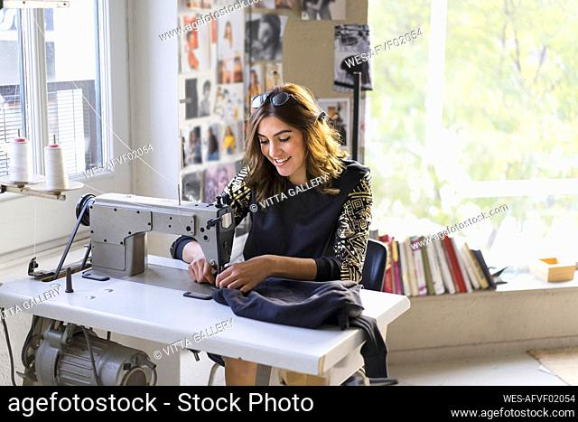 Smiling young fashion designer using sewing machine in her atelier