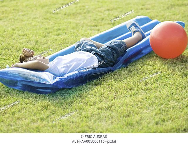 Boy sleeping on water mat on grass