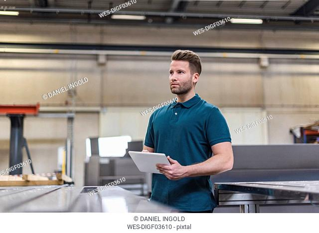 Man with tablet on factory shop floor looking around