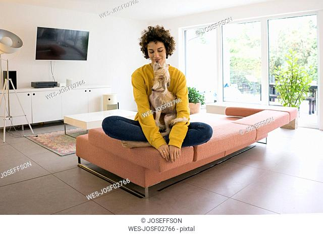 Woman with dog sitting on couch at home