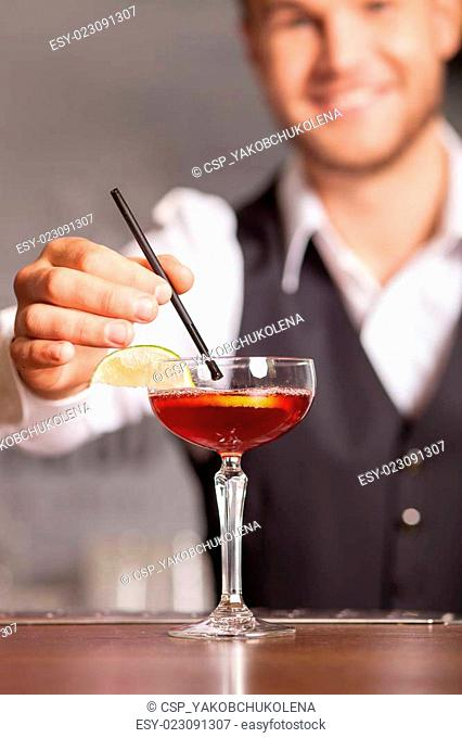 Cheerful young barman is making beverage in bar
