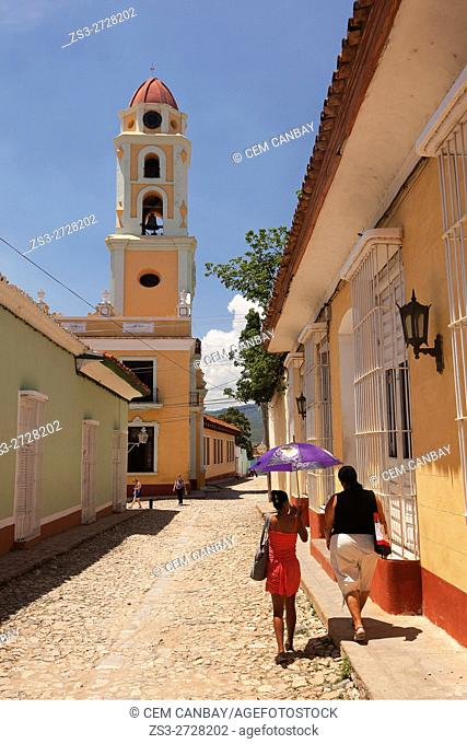 Women with umbrella walking in the cobblestone streets of the main square-Plaza Mayor with the Museo Nacional de la Lucha Contra Bandidos-National Museum of the...