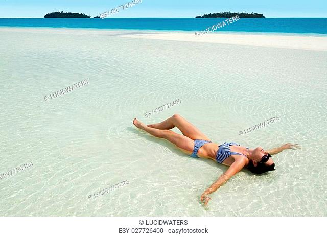 Sexy, tanned young woman tanning on Aitutaki Lagoon, Cook Islands