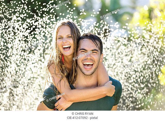 Couple playing in sprinkler in backyard