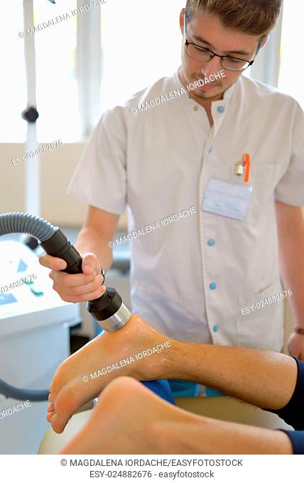 Physiotherapist performs ultrasound physical therapy treatment