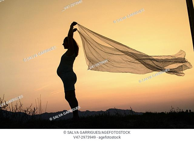 Pregnant woman in profile with a veil flying in the wind at Cullera beach, Valencia, Spain
