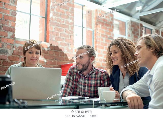 Male and female team looking at laptop at boardroom table meeting in creative studio