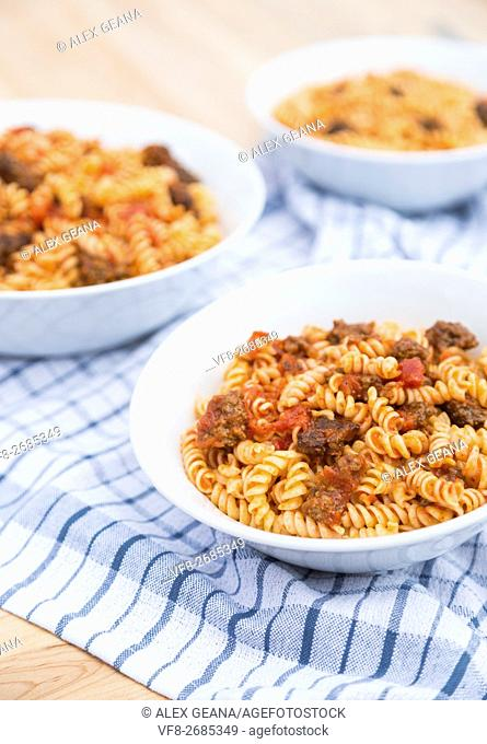 Three bowls of Fusilli pasta, with a tomato meat suace, in white bowls on wodden cutting boards and on a blue checkered napkin