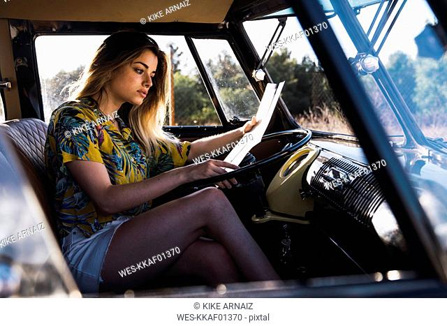Young woman sitting in a van reading map