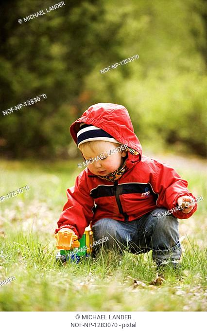 A little girl playing with a toy car outdoors