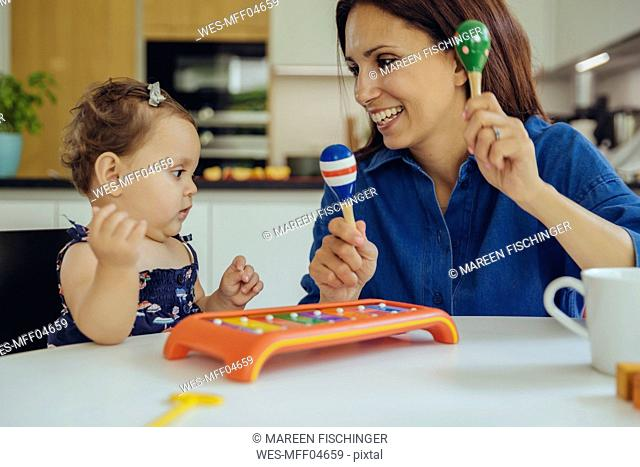 Happy mother and baby daughter playing with rattles