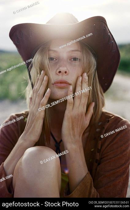 Close-up face of hippie woman in cowboy hat at sunset in meadow
