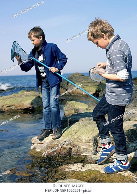 Sweden, Scania, Simrishamn, two boys (12-13) fishing at coast