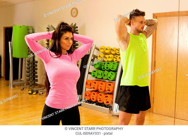 Man and woman in gym standing with hands behind head