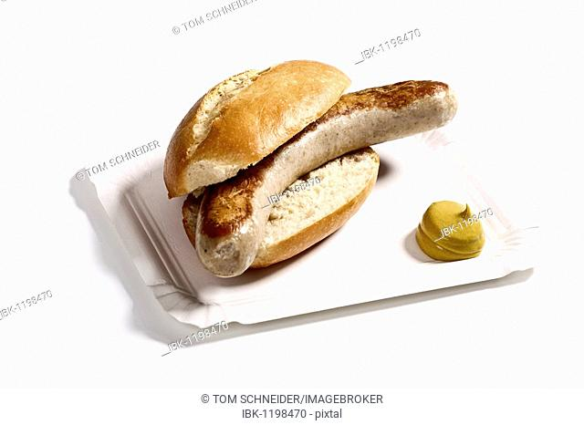 Bratwurst sausage in a bun with mustard on a paper plate
