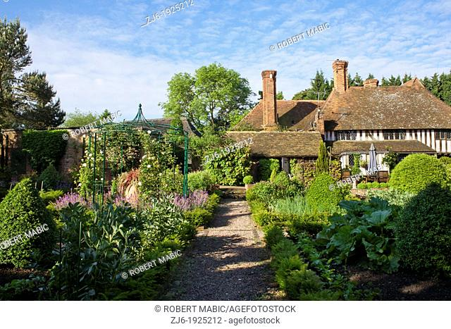 View of the garden, kitchen garden, box topiary, gravel path, house and relaxing area, Bexon Manor Kent England