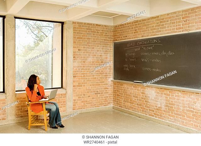 Female student sat working alone