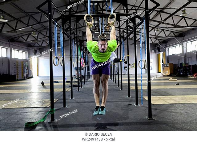 Man doing gym exercise on rings in gym