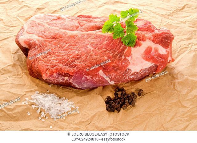 raw marbled pork steak with coarse salt, pepper and parsley