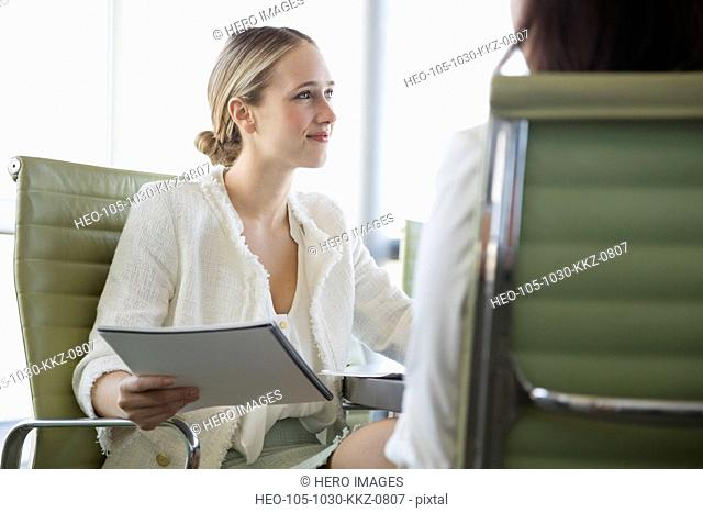 Young businesswoman looking away while holding file in office