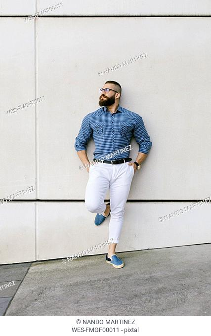 Bearded hipster businessman wearing glasses and plaid shirt leaning against wall