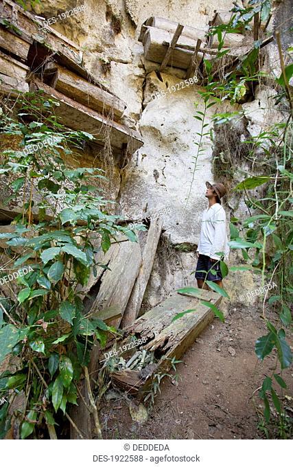 a tourist looks up at hanging coffins on cliffs near the mountain village of sagada, cordillera region, north luzon, philippines