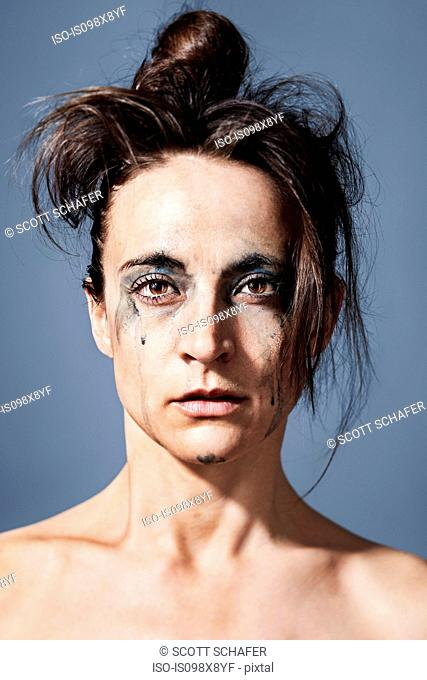 Portrait of a crying woman with make up running down her face