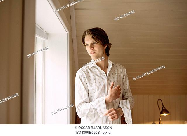 Man getting dressed looking out of window
