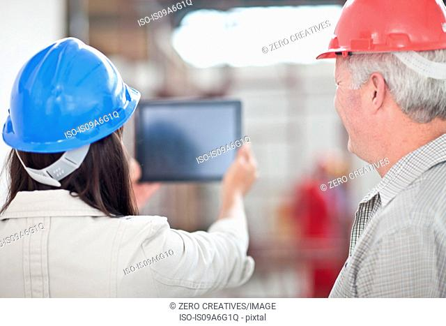 Back view of co-workers looking at digital tablet on construction site