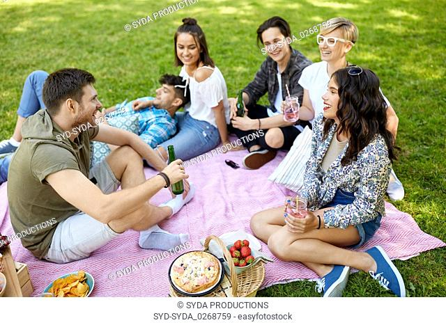 happy friends with drinks at picnic in summer park