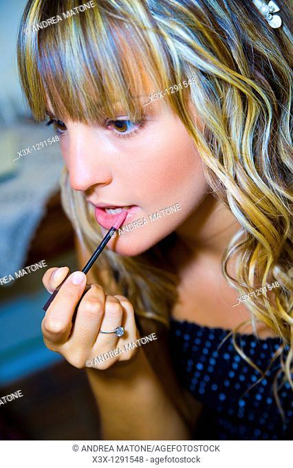Young woman applying lipgloss