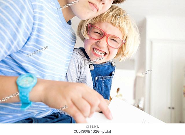 Girl pulling face whilst reading with brother in kitchen