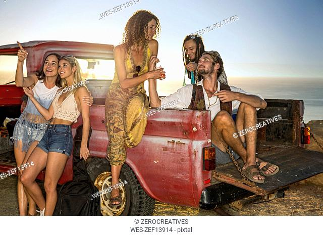 Happy young people outside pick up truck at the coast