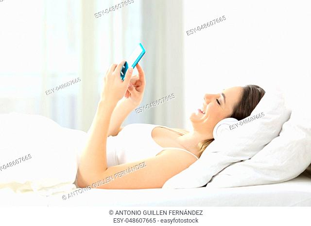 Side view portrait of a woman listening to music and using a smart phone lying on a bed at home