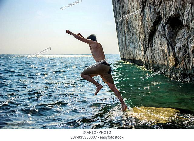 Attractive young shirtless athletic man jumping in water by sea or ocean shore, wearing shorts