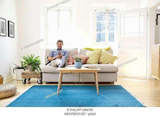 Man sitting on couch at home, using smartphone
