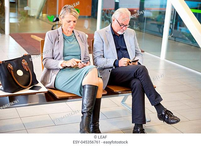 Senior business couple using mobile phones while sitting on chairs in airport waiting area