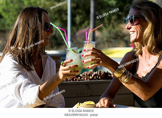 Happy girlfriends sitting outdoors clinking cocktail glasses