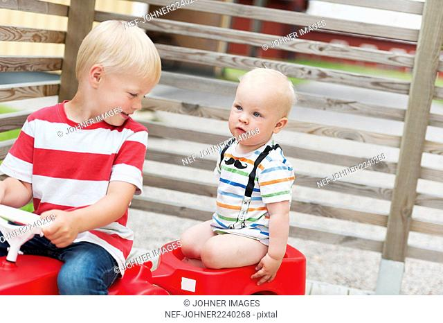 Brothers playing on ride-on car