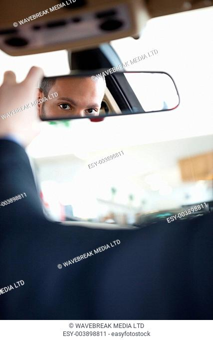 Man adjusting a rear view mirror while sitting in a car