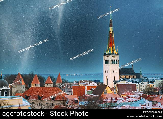 Tallinn, Estonia. Night Starry Sky Above Traditional Old Architecture Skyline In Old Town. Church Of St. Olaf Or Olav In Winter Evening Night