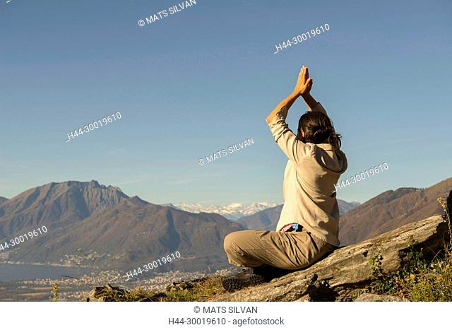 Woman Doing Yoga on the Top of the Mountain in a Sunny Day in Ticino, Switzerland