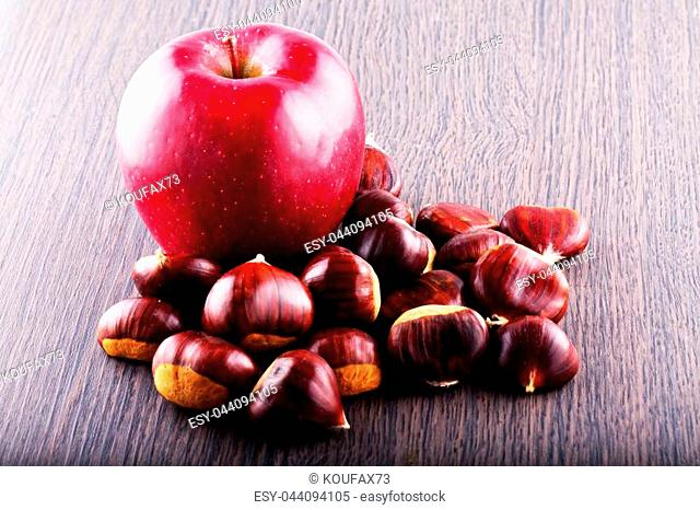 Apple and chestnuts over wooden table, horizontal image