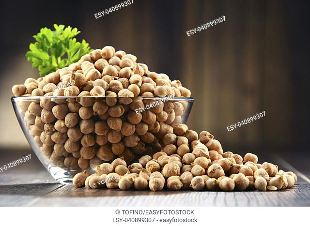 Composition with bowl of chickpeas on wooden table