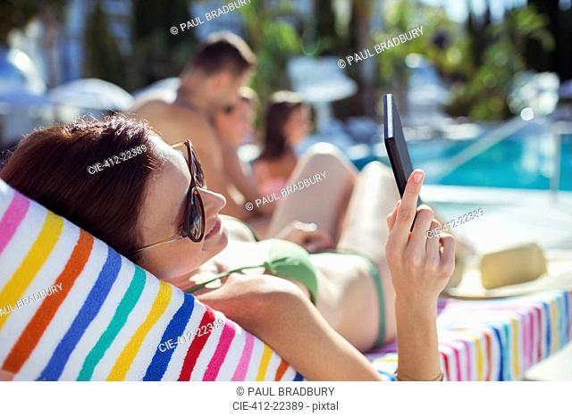 Woman sunbathing and texting by swimming pool