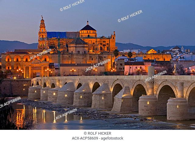 Puente Romano bridge spanning the Rio Guadalquivir river and the Mezquita Cathedral-Mosque during dusk in the City of Cordoba, UNESCO World Heritage Site