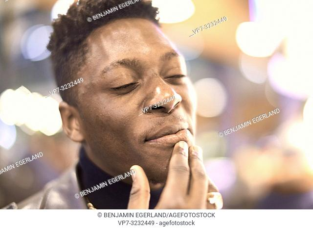 headshot of young man in city lights with closed eyes and positive mindset, African descent, candid happy emotion, inner world, in Munich, Germany