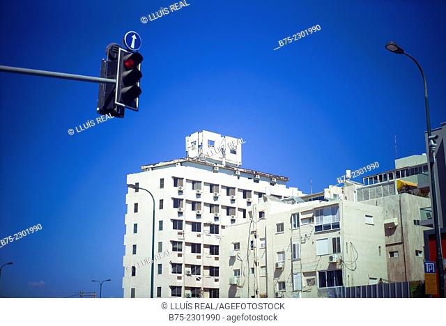 Several buildings with air conditioners in the windows and a traffic light in the foreground, with a directional arrow and several streetlights in Tel Aviv